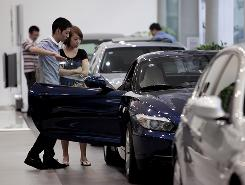 Customers look at a BMW Z4 car at a dealership in Shanghai. China last year surpassed the U.S. as the world's largest automobile market.