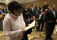 Cami Tolbert views employment information while attending a Global Recruiting Solutions job fair in Livonia, Mich., in September.