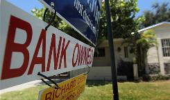 A bank-owned sign is seen in front of a foreclosed home July 29 in Miami.