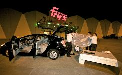 Fry's Electronics sales associates help a customer load a 55-inch television set into the back of his Toyota Prius in Burbank, Calif.