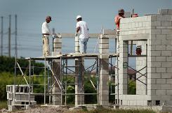 Construction workers build a home in Cooper City, Fla.