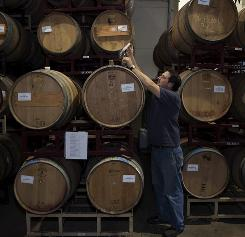 Winemaker Brad Smith checks some barrels at Silenus winery in Napa Valley, recently bought by Chinese investors.
