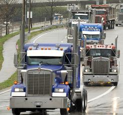 Truckers drive down Greenbrier Street in Charleston, W.Va., to rally against high fuel prices on April 4, 2008. New fuel consumption rules could raise the costs of trucks and engines.
