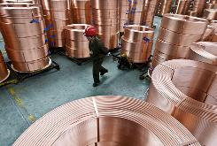 A worker moves piles of copper tubes at a factory in Zhuji, in east China's Zhejiang province.