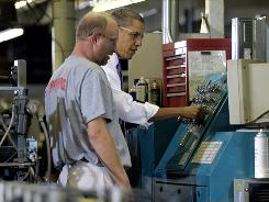 President Obama pushes buttons on a machine as he talks to a Stromberg Metal Works employee during a tour of the company in Beltsville, Md., Friday, Oct. 29, 2010, before speaking about the economy.