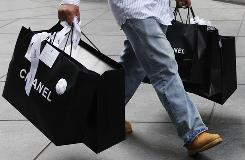 A man carries Chanel shopping bags, in New York in this file photo.