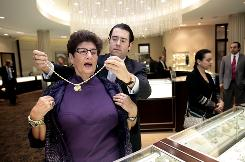 "Tapper's Diamonds and Fine Jewelry owner Mark Tapper puts a $65,000 Judith Ripka diamond heart necklace on shopper Rosemary Stepanski in Troy, Mich. Stepanski has been a Tapper's customer since 1977. Tapper expects holiday sales will be good this year. ""We believe in this economy."""