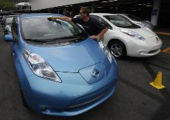 Douglas Cates of Nissan wipes down one of the 14 Leafs available for test drives at Century City mall in Los Angeles. The Leaf gets about 100 miles per charge and is powered only by an electric motor. It's not a hybrid.