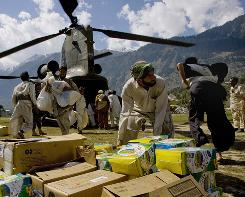 Getting help: In this picture taken on Sept. 29, Pakistani volunteers unload relief supplies from a U.S. Chinook helicopter in Pakistan's Swat Valley. Monsoon rains this summer caused massive flooding that destroyed several villages and towns, and killed nearly 2,000.