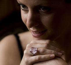 A Sotheby's employee displays a 24.78 carat fancy intense pink emerald-cut diamond ring at Sotheby's in Geneva, Switzerland.