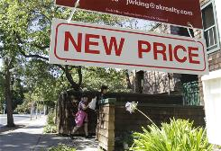 A new-price sign hangs near a home for sale in Palo Alto,