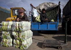 Vendors wait for customers at a vegetable wholesale market in Beijing. A jump in food costs drove China's inflation to a 25-month high in October, raising the possibility the government might impose controls that could slow economic growth.