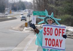 Erin Steenson of Oakton, Va. works as a roadside marketer for Liberty Tax Service, which hires 33,000 seasonal tax preparers and marketers. File photo.