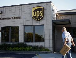 A customer walks into a UPS shipping center.