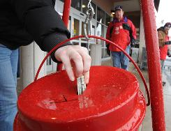 A donor drops money into a Salvation Army bucket outside a Clifton, Va., store in 2009.