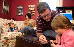 Joe Voris helps his 16-month-old daughter, Emma, with the Roku remote as his wife, Amy, 37, and son, Evan, 7, sit on the couch.