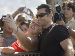 A fan takes a photo with actor Hugh Jackman after a 2009 press conference in Rio de Janeiro.