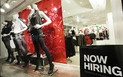 "A ""now hiring"" sign sits in the window of an Express clothing store in New York."
