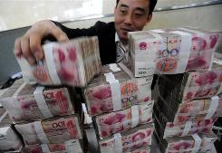 A clerk stacks up banknotes at a bank in Hefei in central China's Anhui province.