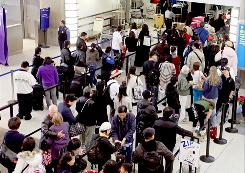 Travelers wait in line at Los Angeles International Airport during last year's holiday season.