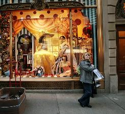 A shopper on Fifth Avenue passes the Henri Bendel holiday window display Nov. 19, 2010 in New York City.