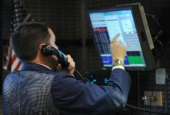 A stock specialist works at a trading post on the floor of the New York Stock Exchange.