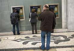 People use automated teller machines in downtown Lisbon, Portugal.