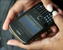 A woman uses a BlackBerry phone.