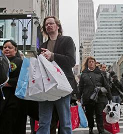Shoppers cross a street outside Macy's in Manhattan,