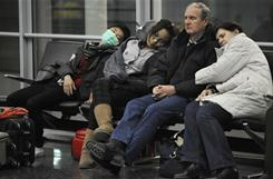 Passengers sleep in the United Airlines terminal at Chicago's O'Hare airport after a winter storm earlier this month canceled flights.