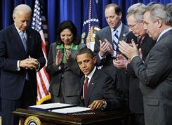 President Obama signs into law an $858 billion bill extending for two years Bush-era tax cuts. Vice President Biden, left, and members of Congress and administration officials attend the Dec. 17 ceremony.