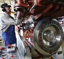 In this Feb. 17,2009, file photo, an engine technician works on a vessel engine at Caterpillar in northern Germany.
