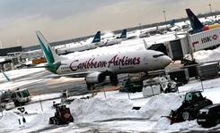 A Caribbean Airlines flight sits near machinery moving snow on Tuesday at New York JFK.