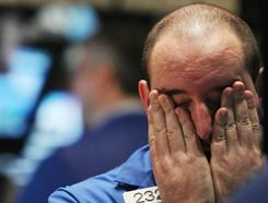 A trader rubs his eyes on the floor of the New York Stock Exchange in May 2010. Investors experienced another volatile year as more cash was pulled out than put into stock funds.