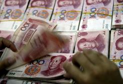 A Chinese bank staffer counts stacks of 100-yuan notes in this file photo.