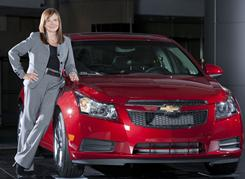 Mary Barra poses with a 2011 Chevrolet Cruze at GM World Headquarters in Detroit in this file photo.