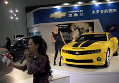 A model poses next to a Chevrolet Camaro on display at an auto show in Beijing on Nov. 20, 2009.