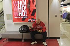 Customer Victor Mercado of Brooklyn check's the store's flier at the Manhattan Mall J.C. Penney store in New York in December 2010,