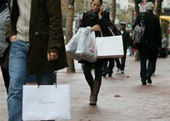 A pedestrian carries shopping bags while walking on Market Street in San Francisco on Dec. 14, 2010.