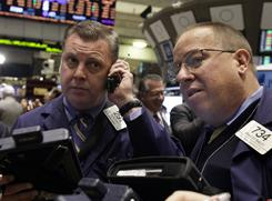 Traders Matthias Roberts, left, and Bradley Bailey work on the floor of the New York Stock Exchange Friday, Jan. 28, 2011.