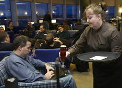 Hostess Connie Davis delivers beer to James Miller at the British Airways Terrace Lounge at Seattle-Tacoma International Airport.