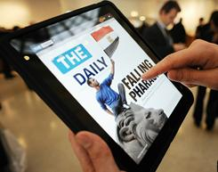 A journalist looks at the front page of The Daily, an electronic newspaper designed for the iPad, after its launch Feb. 2, 2011.