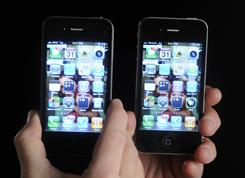 The AT&T, left, and Verizon iPhone 4s look virtually the same. The network performance is what distinguishes the two.