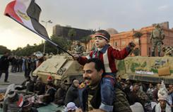 A young anti-government protester sitting on the shoulders of a relative waves the Egyptian flag in front of Egyptian Army armored personnel carriers at a protest in Tahrir Square in Cairo on Feb. 7, 2011.