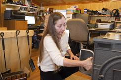 In this Jan. 22, 2011, photo, Valerie Houde fills her wood stove while waiting for a dial-up Internet connection in East Burke, Vt.