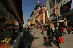 Shoppers walk through a busy retail street in Beijing on Feb. 14, 2011.