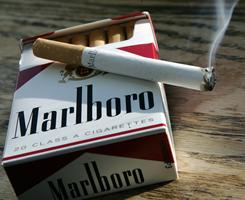 A cigarette burns as it sits on a pack of real Marlboro cigarettes in this file photo.