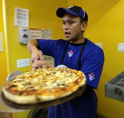 West Lopez takes a pizza from the oven at Domino's in Farmington Hills, Mich., in this file photo. The company has revamped its chicken menu.
