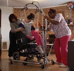 April Quinn, right, and Holly Hawthorne's mother, Diane Allison, help Holly out of bed and into her wheelchair using a sling at Diane's home on Feb. 11.