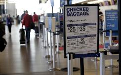 An American Airlines sign showing baggage fees at Seattle-Tacoma International Airport.